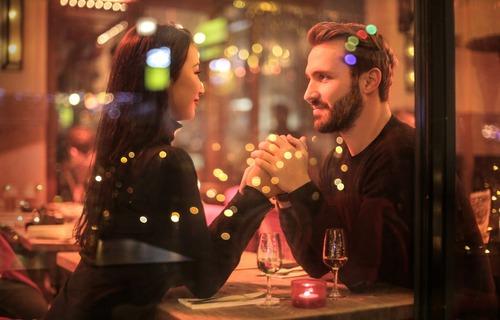 Casal em clima de romance visto do lado de fora em um restaurante.