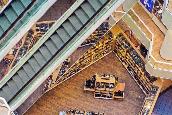 Foto em perspectiva de cima para baixo: acima, escada rolante; abaixo, loja de vinhos.
