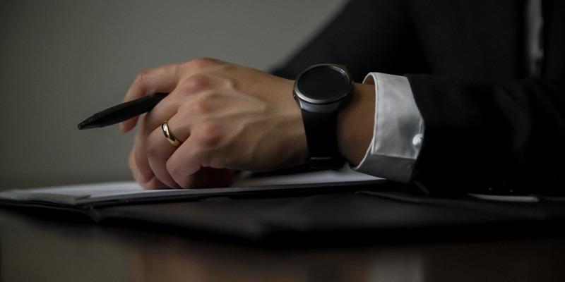 Mãos masculinas sobre pasta em cima da mesa. A pessoa usa terno, relógio, aliança e segura uma caneta.