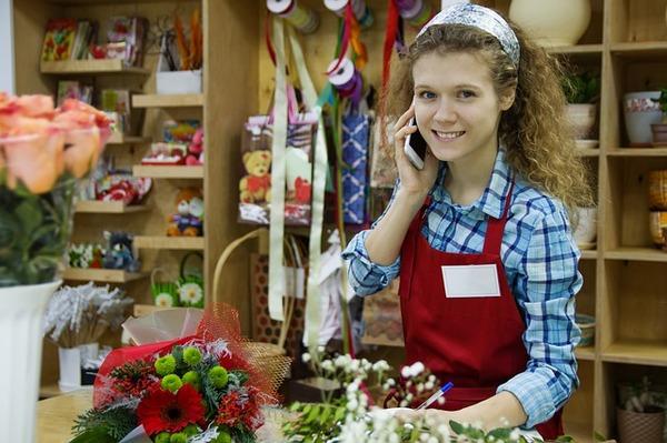 Mulher jovem atrás de balcão de loja de flores, presentes e artesanatos. Ela sorri e fala ao telefone.