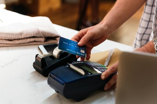 Em foco, uma pessoa escolhe as formas de pagamento e realiza venda na maquininha de cartão.