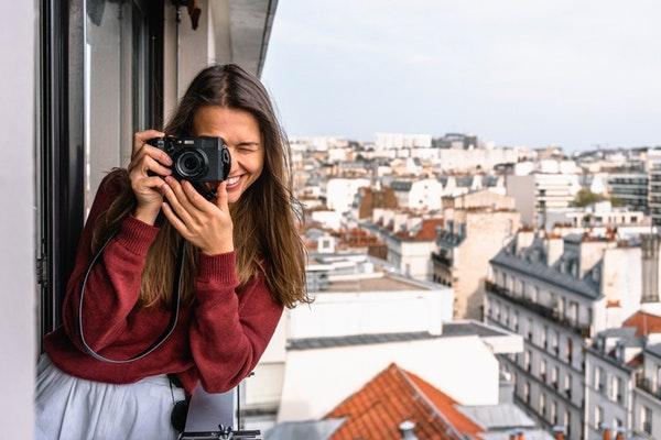 Mulher sorrindo e tirando foto com câmera digital em uma sacada. Ao fundo, vê-se os prédios da cidade.