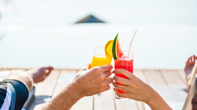 Homem e mulher fazendo um brinde com bebidas coloridas em deck.
