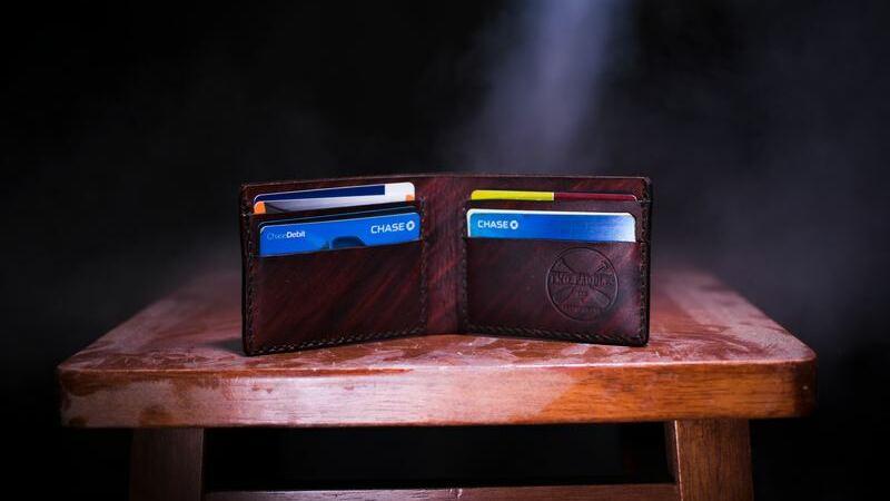 Carteira aberta sobre banco de madeira mostrando cartões do Morgan Chase Bank.