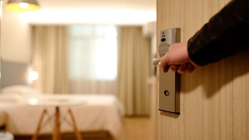 Em foco, mão abrindo porta de quarto de hotel. Desfocado, o quarto possui uma cama, uma mesa pequena, cortinas e luminárias.