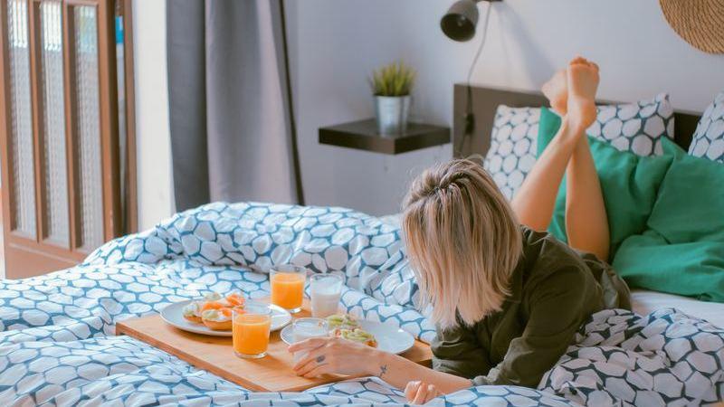 Mulher loira deitada em cama de hotel. À sua frente, uma bandeja com um café da manhã completo.