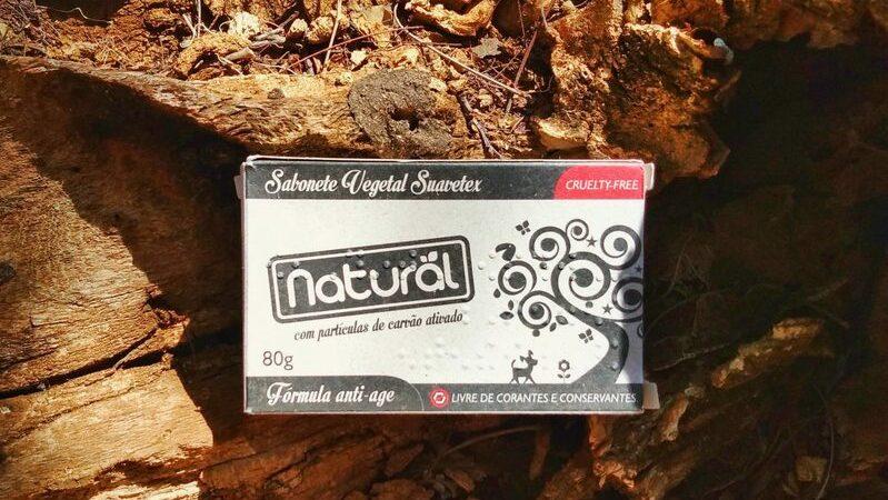 Caixa de sabonete vegetal de carvão ativado da linha Orgânico Natural da Suavetex sobre pedaços de madeira seca.