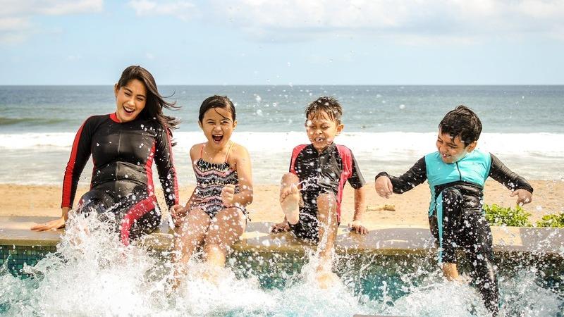 Crianças sentadas em borda de piscina agitando os pés na água com expressão feliz e animada