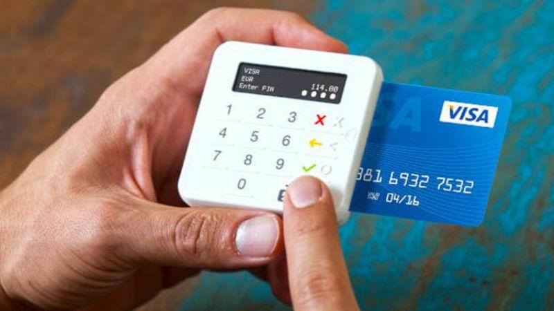 Mini maquininha sendo segurada por pessoa que digita a senha do seu cartão.