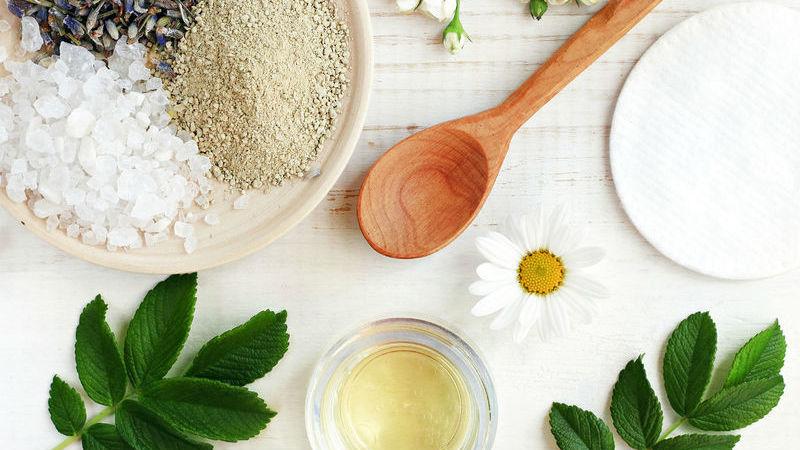 Ingredientes para produção de cosméticos e produtos naturais sobre superfície branca.