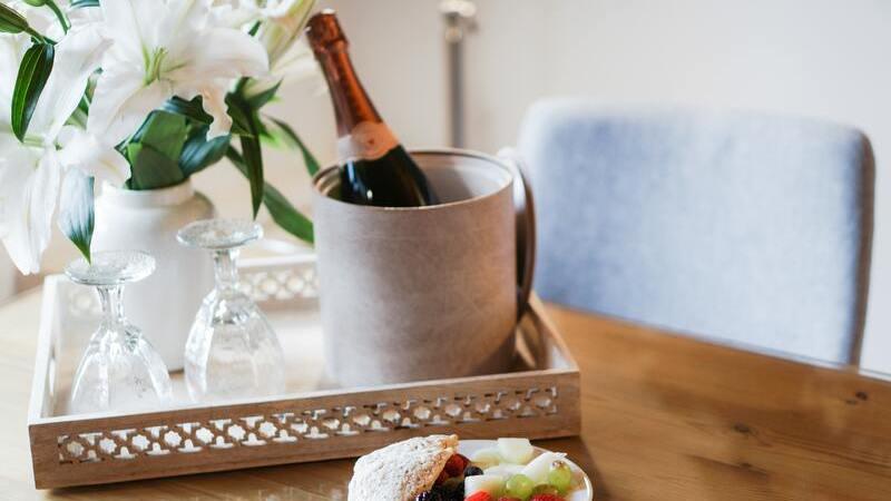Bandeja com champanhe no balde, taças de vidro e jarro de flores sobre mesa de quarto de hotel. À frente, prato com frutas.