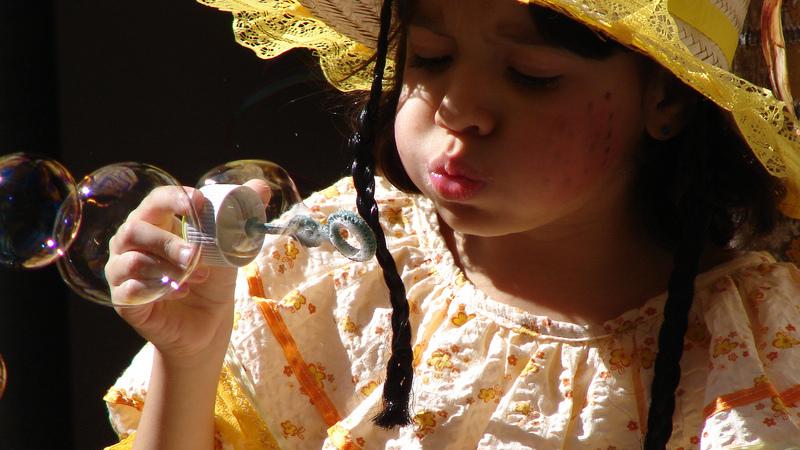 Menina vestida de caipira para Festa Junina, soprando bolhas de sabão.