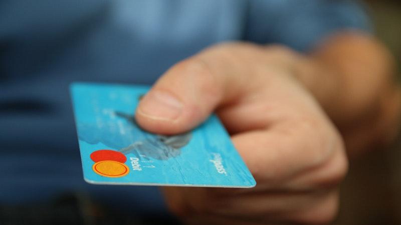 Pessoa segurando um cartão de débito azul.
