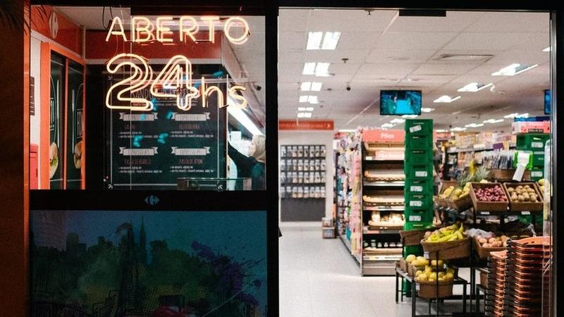 """Carrefour bairro visto de fora, com a porta aberta, e um letreiro de neon que diz """"Aberto 24hs"""" colado no vidro da porta."""