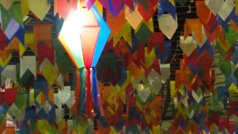 Diversos varais de bandeirinhas coloridas e alguns balões de Festa Junina pendurados.
