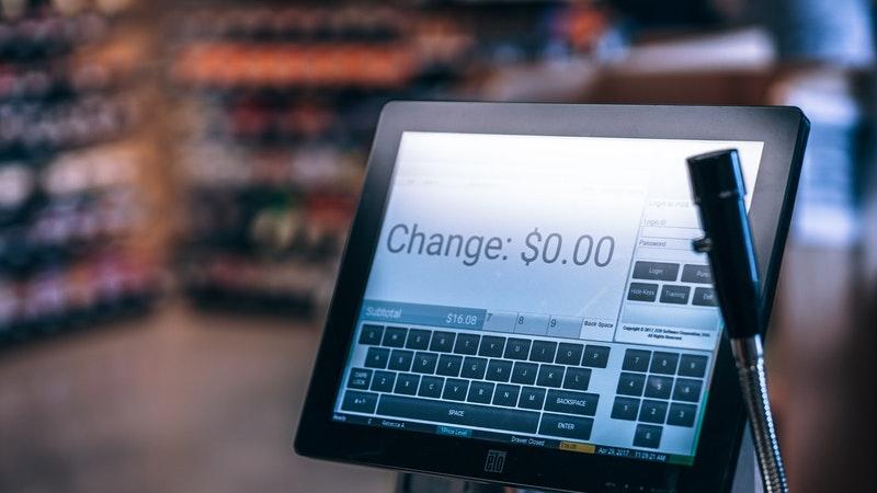 """Computador em caixa da loja com display dizendo """"zero de troco"""". Ao fundo, um supermercado moderno com desfoque."""