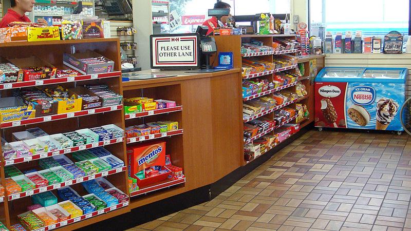 Caixa da loja de conveniência com vários doces à disposição e dois funcionários.