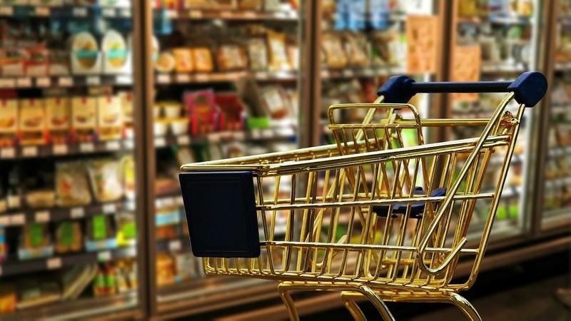 Carrinho de compras em supermercado, ao lado da sessão de frios.