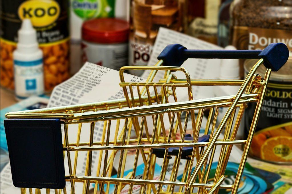 Carrinho de compras cercado de produtos com lista ao fundo
