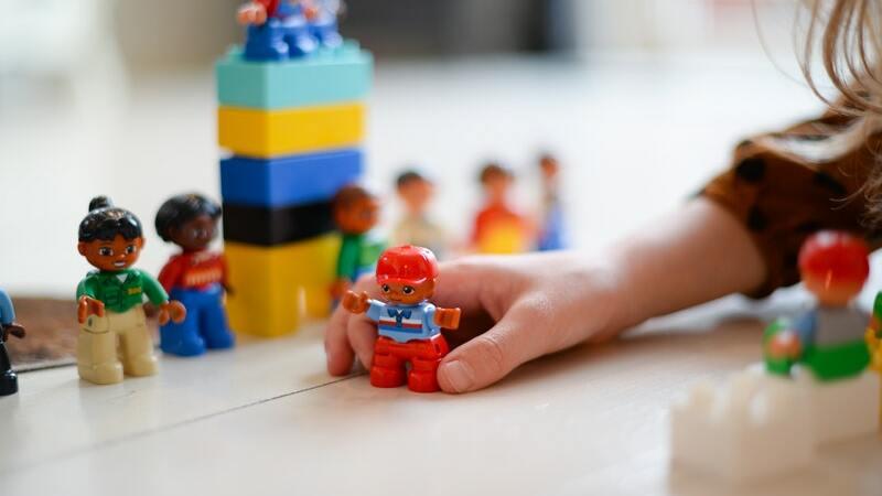 Mãos de uma criança brincando com boneco de Lego. Ao lado e ao fundo, mais peças.