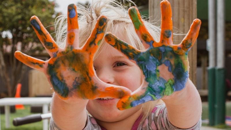 Criança pequena mostra as mãos espalmadas cheias de tintas coloridas.