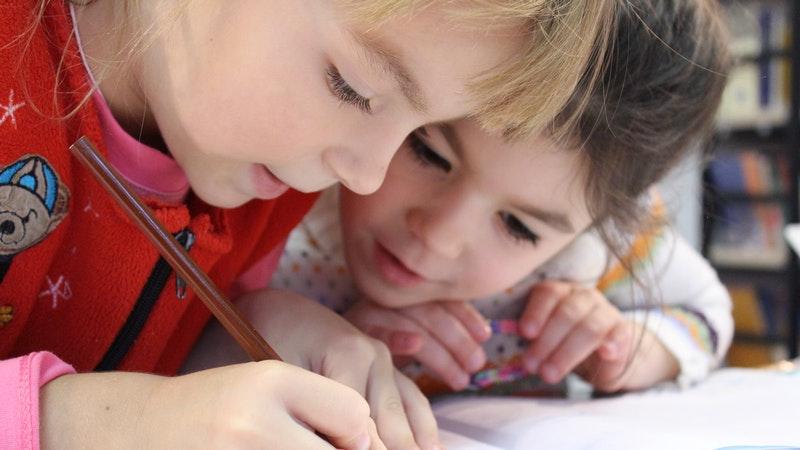 Em foco, duas crianças inclinadas sobre um caderno. Uma delas escreve de lápis e a outra observa com atenção.