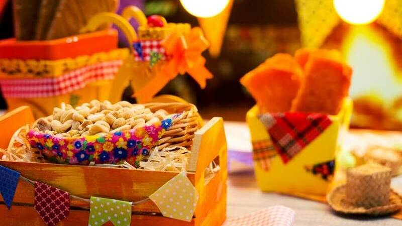 Foto com vários produtos para Festa Junina e comidas típicas sobre superfície.