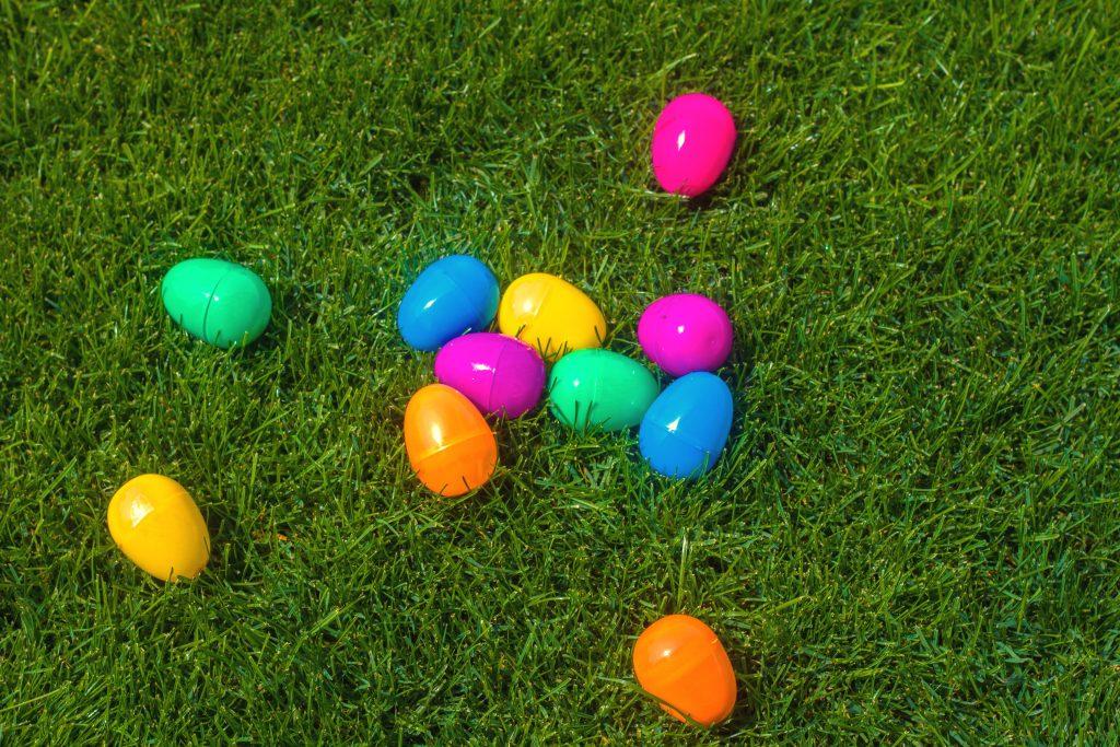 Ovos de plástico coloridos sobre campo de grama