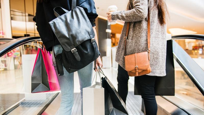Duas amigas fazem compras em shopping e descem pela escada rolante.