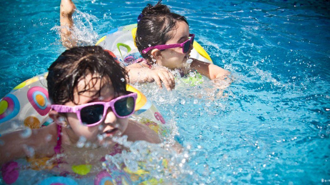 Duas crianças com boias e óculos escuros nadando em piscina.