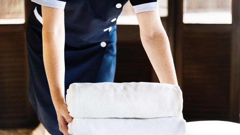 Camareira deposita toalhas brancas em cima de uma cama.
