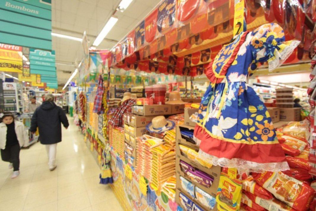Em foco, ilha temática de supermercado com itens de festa junina. No fundo, clientes andam pelos corredores.