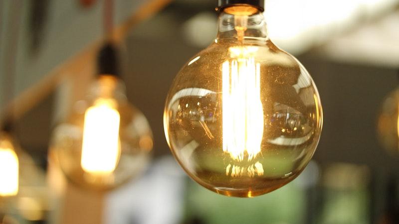Lâmpada bulbo de LED transparente fumê acesa em close. Ao fundo e com desfoque, outras lâmpadas também acesas.