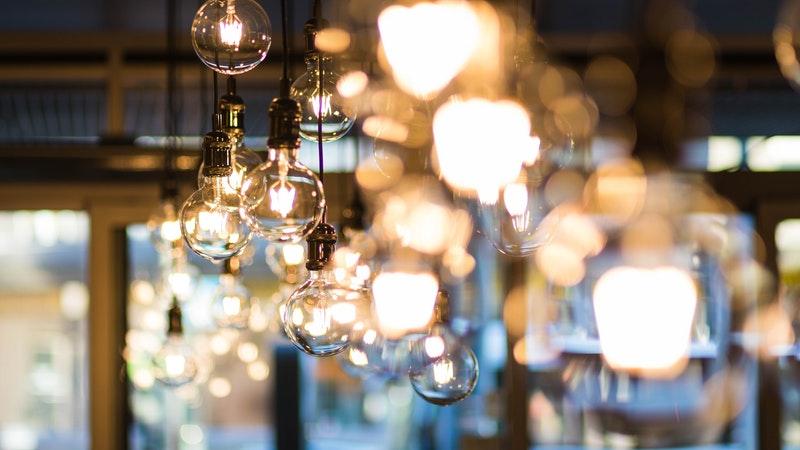 Várias lâmpadas de LED transparentes fumê penduradas em expositor de loja de materiais elétricos.
