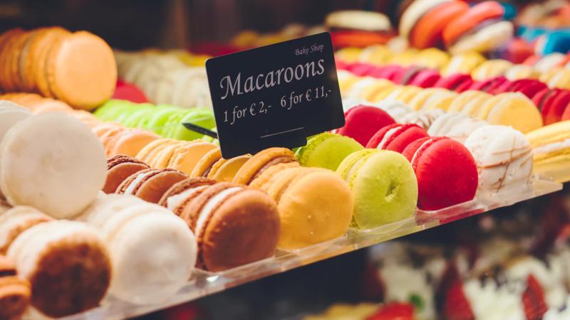 Macarons coloridos em vitrine com placa indicando seu preço. 1 por 2, 6 por 11