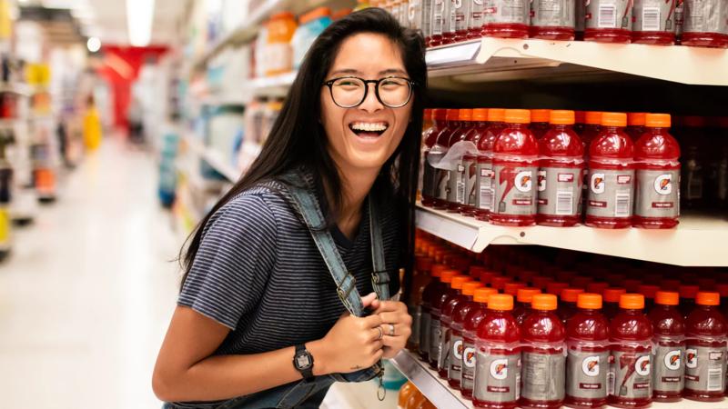 Mulher sorridente ao lado de gôndola de um supermercado moderno.