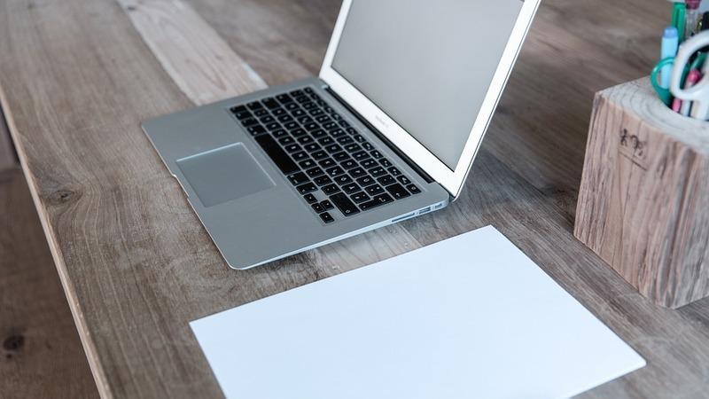 Notebook aberto sobre mesa de madeira. Ao lado, uma folha em branco e um porta-canetas também de madeira.