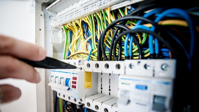 Painel de circuitos e ligações elétricas sendo operado por mão com chave de testes.