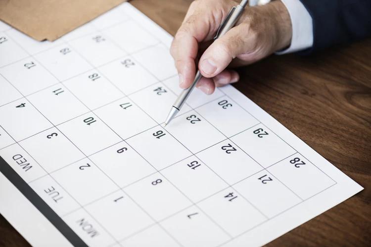 Black Friday, Black Week e Cyber Monday: pessoa com caneta em calendário.