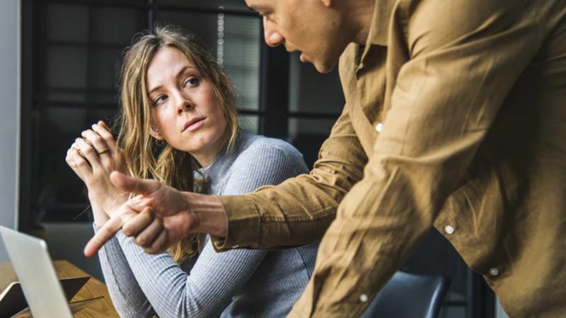Como gerenciar loja: mulher recebendo instruções de homem apontando para tela