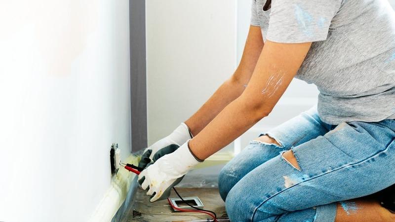 Mulher testando tomada com um multímetro. Há um pequeno buraco na tomada. A mulher está suja de tinta e usa luvas.