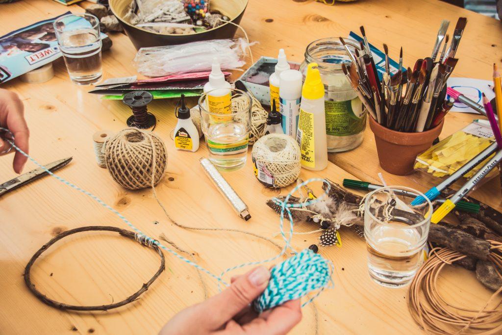Sobre uma mesa, vários produtos para fazer artesanato e mão desenrolando carretel de fios.