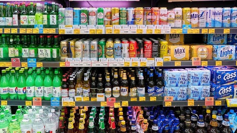 Refrigerador de loja de conveniência com diferentes latas e garrafas de bebida