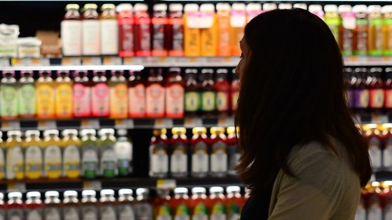 Pessoa passeado por prateleira refrigerada de bebidas em supermercado