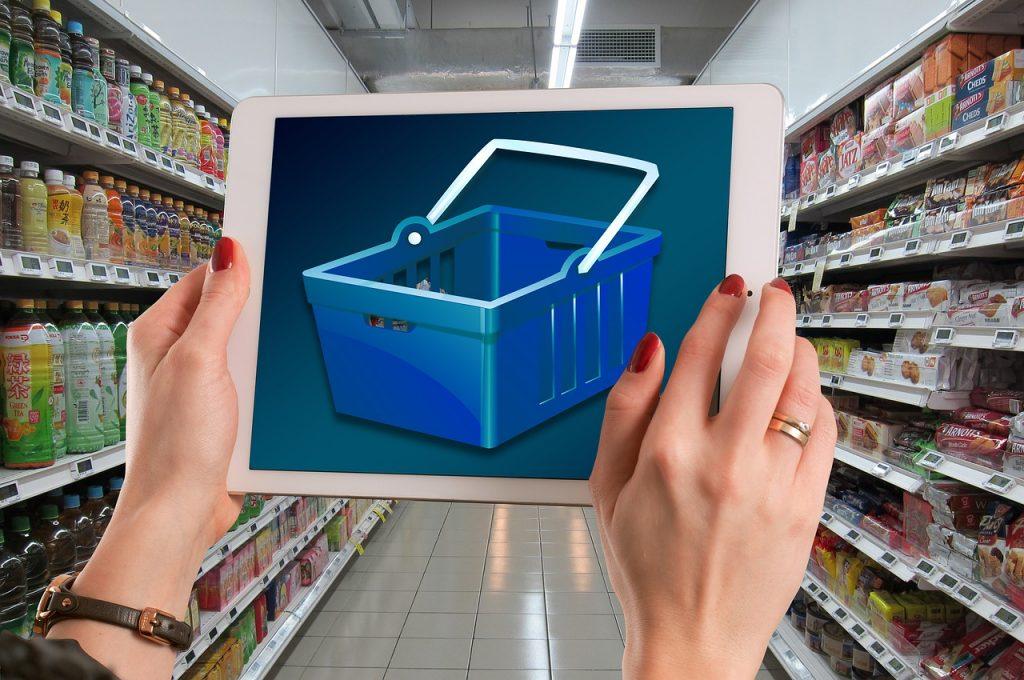 Mãos segurando um tablet com carrinho de compras na tela diante de um corredor de mercearia