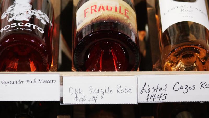 Vinhos expostos em prateleira de adega com etiquetas de preço abaixo deles.