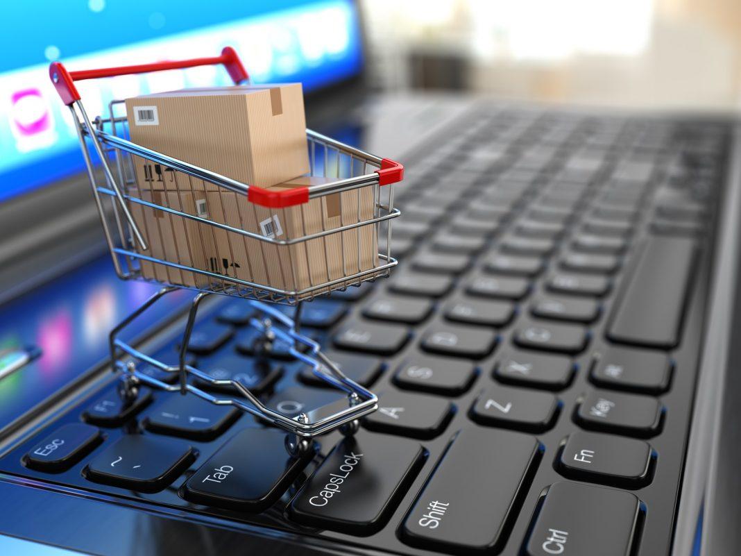 Carrinho de compra com caixas em cima do teclado de computador