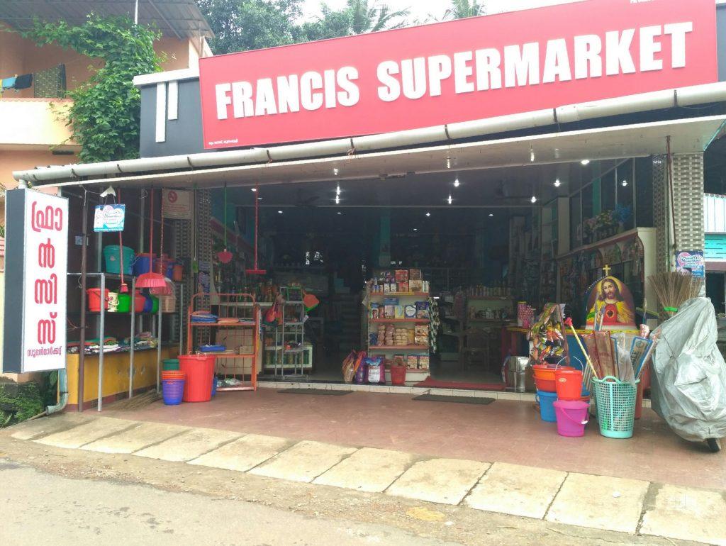 Fachada de mercadinho com faixa vermelha, baldes e utensílios na calçada
