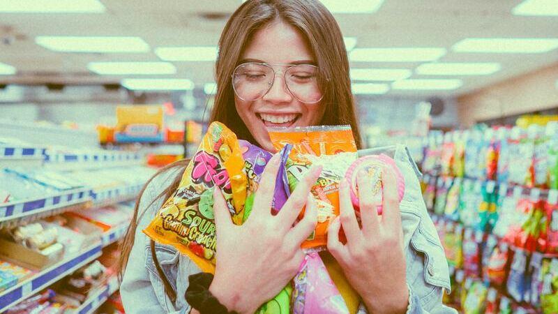 Mulher em corredor de supermercado segurando várias embalagens de doce