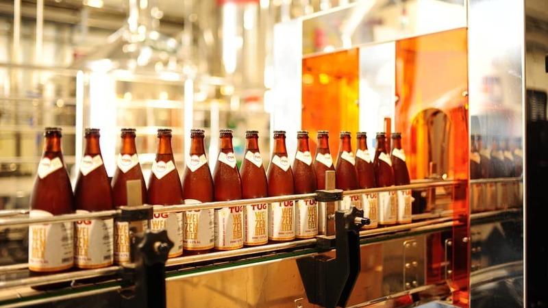 Garrafas de cerveja TUG Weizenbier em esteira de produção na cervejaria.